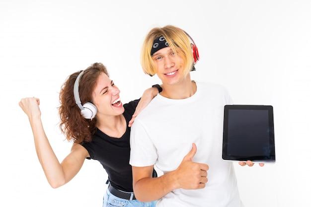Menina emocional inclina-se sobre o ombro de um cara segurando um tablet com uma maquete sobre um fundo branco