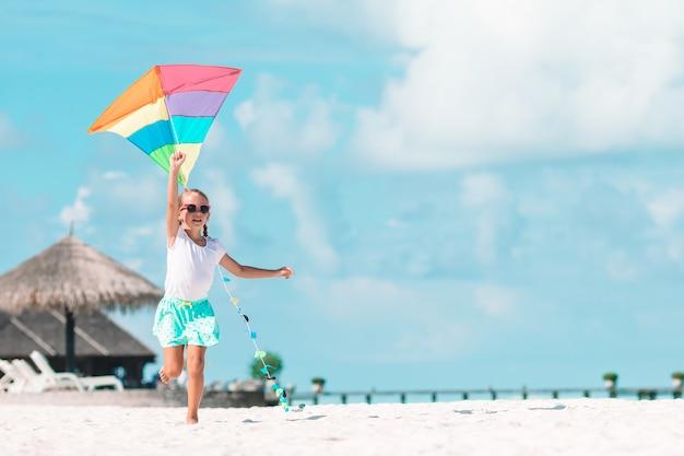 Menina empinando uma pipa na praia com água turquesa