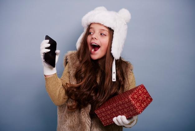 Menina empolgada com celular e caixa de presente