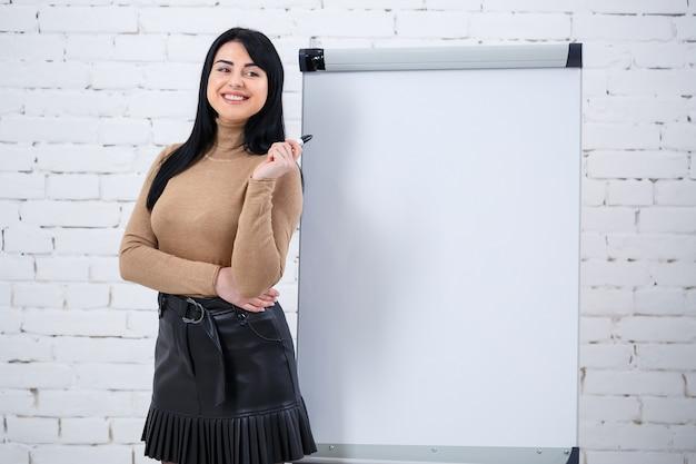 Menina empresária, professora, treinadora ensina e fala sobre um novo projeto em pé perto do quadro-negro