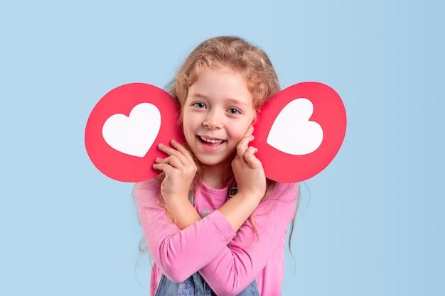 Menina encantada com roupas casuais, mantendo ícones de coração perto do rosto e sorrindo amigavelmente enquanto representa as mídias sociais para crianças
