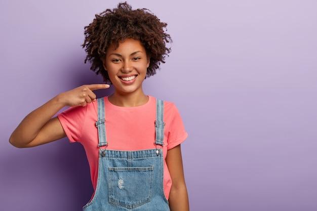 Menina encantada de pele escura sorri amplamente, mostra dentes brancos perfeitos, usa camiseta casual rosa e macacão jeans, está de bom humor, isolada na parede roxa do estúdio