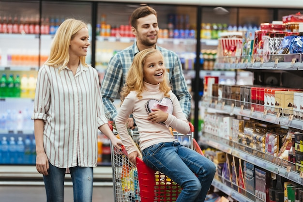 Menina encantada, sentado em um carrinho de compras