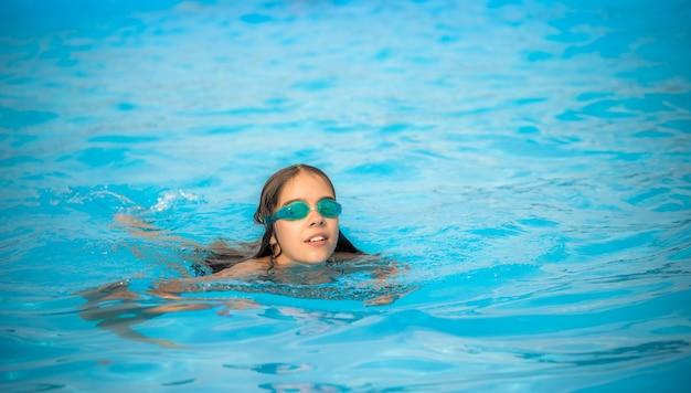 Menina encantadora adolescente usando óculos à prova d'água para nadar na piscina