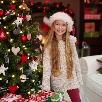 Menina encantadora ao lado da árvore de natal