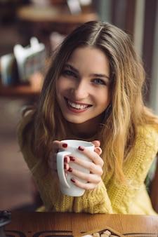 Menina encantadora, bebendo cappuccino e comendo cheesecake