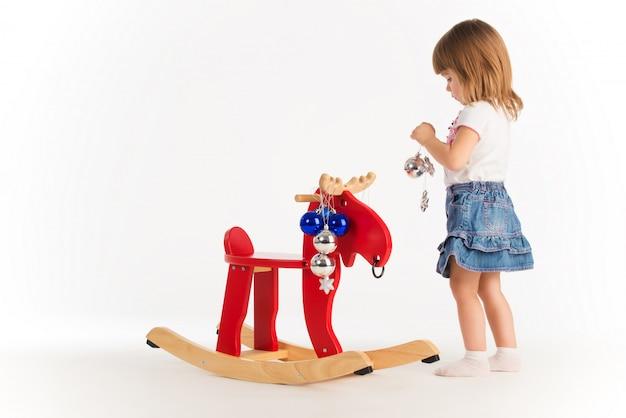 Menina encantadora brinca com um alce de madeira