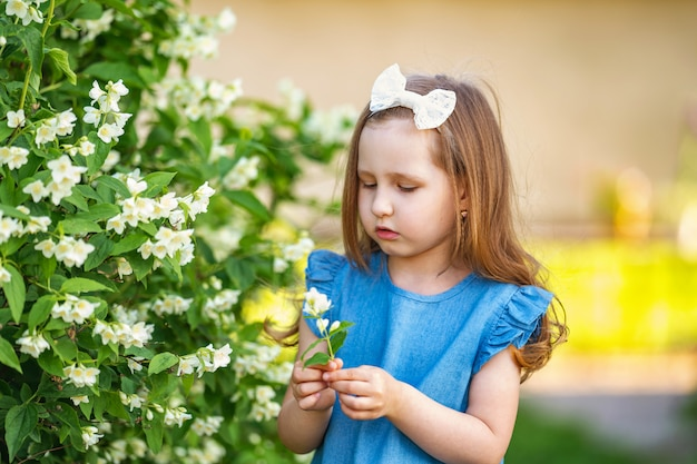 Menina encantadora cheirando flores de jasmim