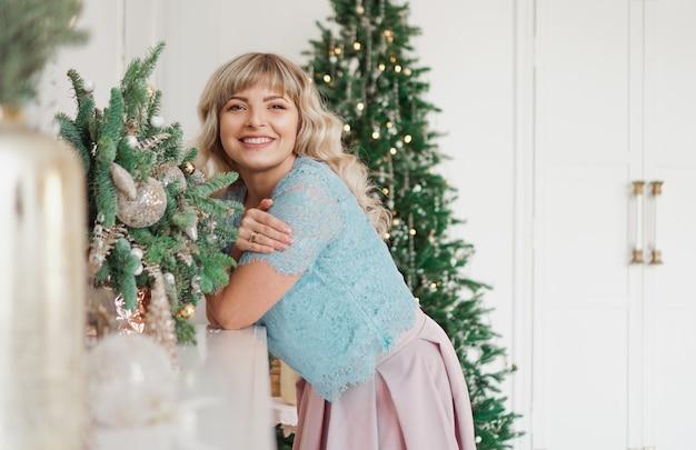 Menina encantadora com bela maquiagem no rosto em ouro e branco interior. férias de natal, feliz celebração com a família Foto Premium