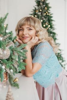 Menina encantadora com bela maquiagem no rosto no interior dourado e branco. férias de natal