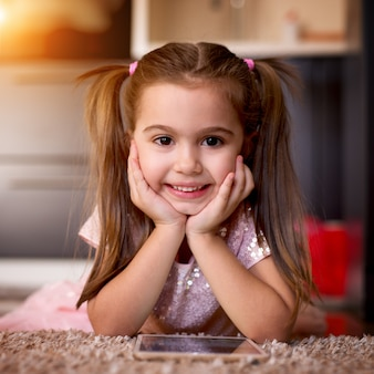 Menina encantadora com bom penteado, olhando para a câmera assistindo desenhos animados