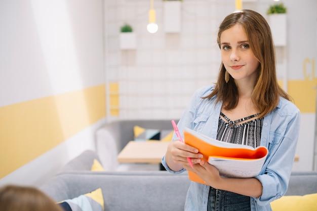 Menina encantadora com caderno posando na câmera