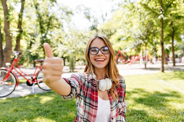 Menina encantadora com camisa quadriculada, posando na natureza. alegre senhora caucasiana de óculos, passando um tempo no parque.