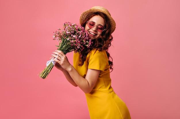 Menina encantadora com chapéu de coco e óculos de sol vermelhos posa com flores cor de rosa