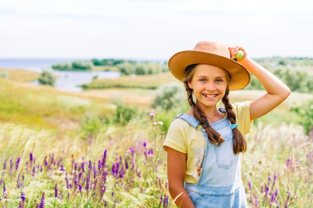 Menina encantadora com chapéu segurando maçãs em uma pitoresca paisagem montanhosa