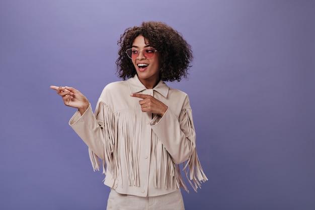 Menina encantadora com jaqueta com franja e óculos mostrando o dedo para o lado