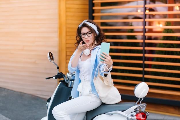 Menina encantadora com penteado encaracolado mandando beijo no ar para a foto, enquanto está sentada na scooter na rua