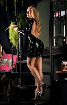 Menina encantadora com pernas longas em vestido de noite, posando na escada.