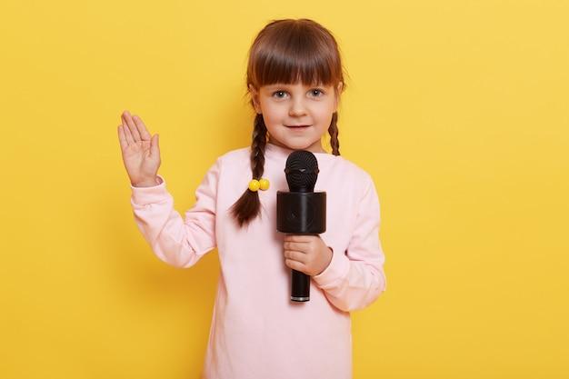 Menina encantadora com rabo de cavalo olhando e segurando o microfone, bonito artista isolado sobre a parede amarela com a palma da mão levantada, criança do sexo feminino vestindo camisa rosa pálido.