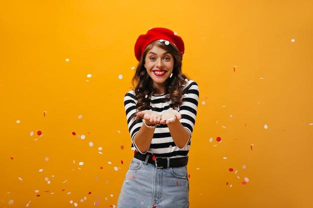 Menina encantadora com roupa elegante joga confete no fundo isolado. mulher legal sorridente na boina vermelha e saia jeans posando.