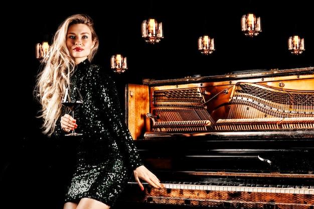 Menina encantadora com um vestido de noite verde posando com uma taça de vinho na mão perto do piano retrô