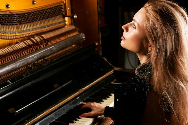 Menina encantadora com um vestido verde gosta de tocar piano retrô