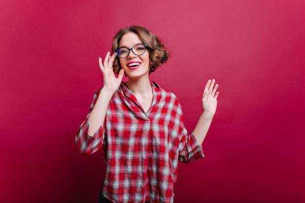 Menina encantadora com uma pequena tatuagem de braço posando na parede claret e rindo. modelo feminino de cabelos castanhos espetacular em copos se divertindo.