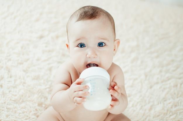 Menina encantadora comendo sozinha uma mistura de leite, mingau segurando uma colher sentada