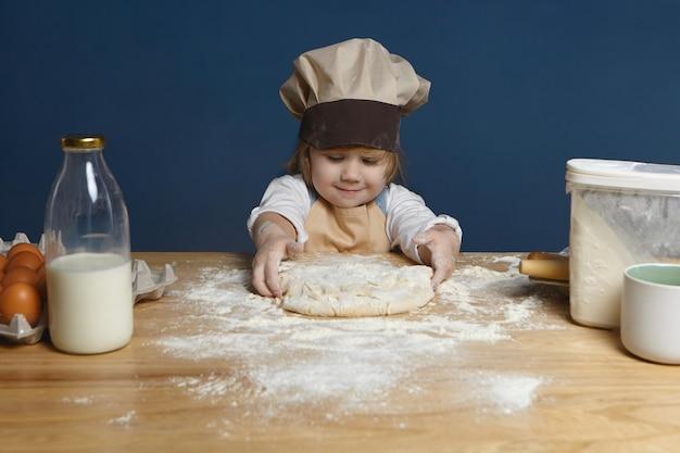 Menina encantadora de 5 anos com chapéu de chef e avental amassando massa no balcão da cozinha