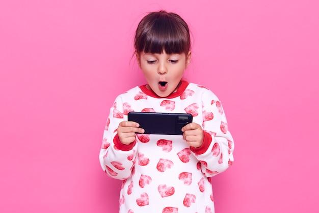 Menina encantadora de cabelos escuros com cabelo escuro, segurando o telefone inteligente com a boca aberta, jogando, sendo surpreendida com o resultado, posando isolado sobre a parede rosa.