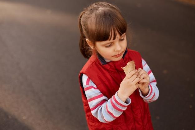 Menina encantadora de jaqueta vermelha, cabelos escuros segurando sorvete nas mãos