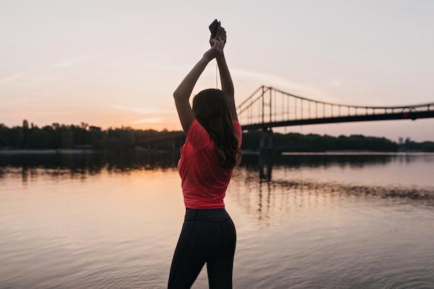 Menina encantadora e bem torneada em pé com as mãos ao alto e olhando para o rio. foto ao ar livre da parte de trás do incrível modelo feminino relaxante após o treinamento perto do lago.