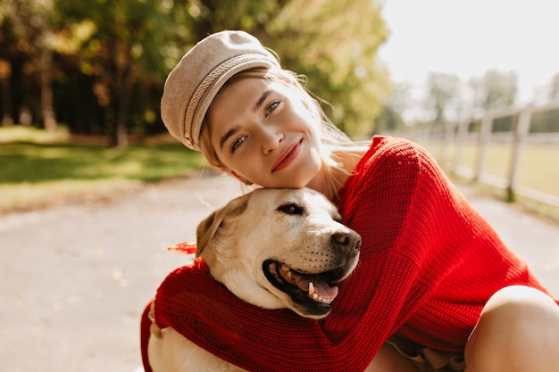 Menina encantadora e seu cachorro se divertindo no parque outono. loira adorável com lindo cão posando.