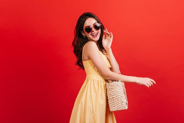 Menina encantadora elegante em vestido xadrez rindo na parede vermelha. foto da modelo feminina usando óculos em forma de coração e bolsa de vime.