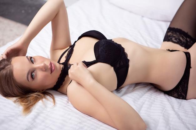 Menina encantadora em roupa íntima de renda preta deitada em uma cama grande