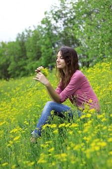 Menina encantadora em um campo dos girassóis que prendem um ramalhete das flores.