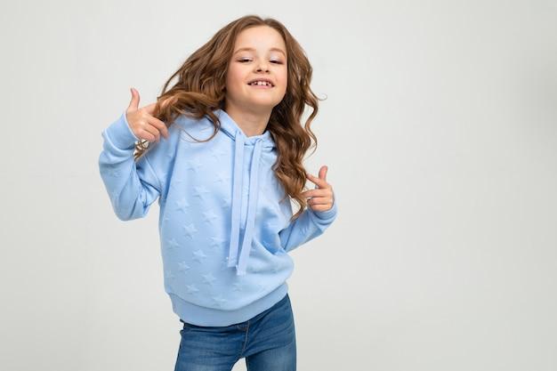 Menina encantadora em um capuz azul posando em uma parede branca com espaço em branco