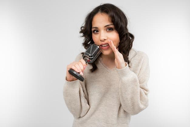 Menina encantadora em um suéter branco tem um microfone retrô na mão e canta uma música em um cinza