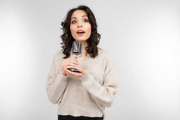 Menina encantadora em um suéter branco tem um microfone retrô na mão e canta uma música em um fundo cinza