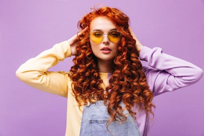 Menina encantadora em vestido de verão jeans e suéter tocando seu cabelo vermelho e fazendo poses usando óculos