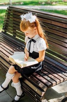 Menina encantadora engraçada com livros nas mãos, no primeiro dia de escola ou jardim de infância. uma criança está sentada em um banco do lado de fora em um dia quente e ensolarado e está voltando para a escola.