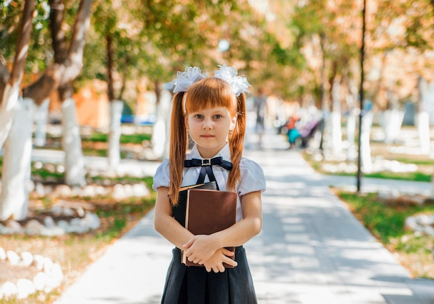 Menina encantadora engraçada com livros nas mãos, no primeiro dia de escola ou jardim de infância.