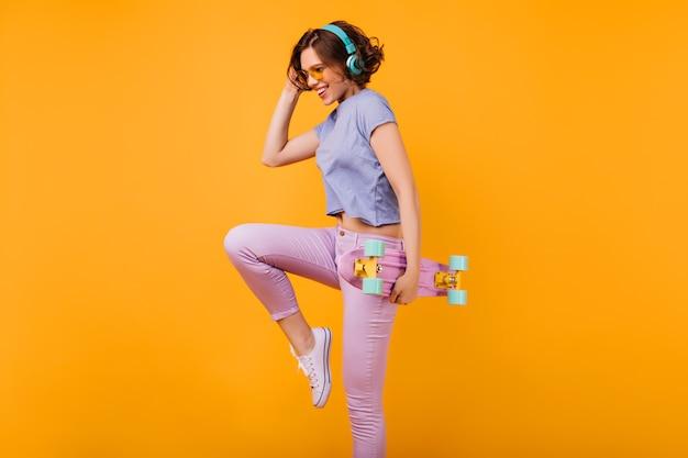 Menina encantadora magro em fones de ouvido azuis dançando com um sorriso. modelo feminino bem torneado com longboard, saltando com expressão de rosto feliz.