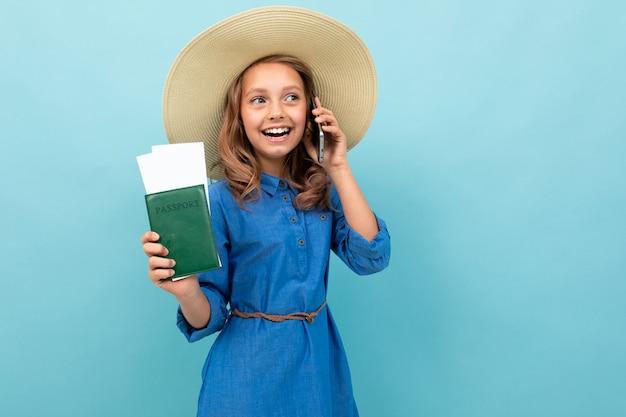 Menina encantadora mostra um passaporte com bilhetes, fala ao telefone e se alegra