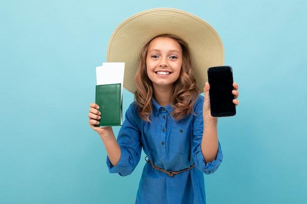 Menina encantadora mostra um passaporte com bilhetes, telefone e se alegra