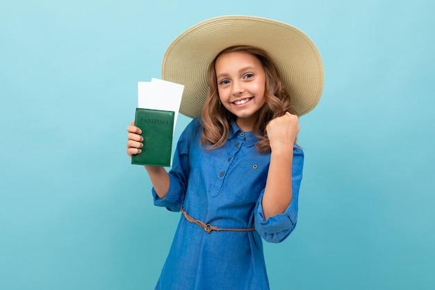 Menina encantadora mostra um passaporte com ingressos e se alegra