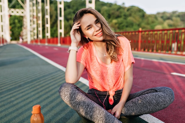 Menina encantadora ouvindo música em fones de ouvido após a maratona. retrato ao ar livre da magnífica mulher desportiva sentado na pista de concreto com um sorriso.
