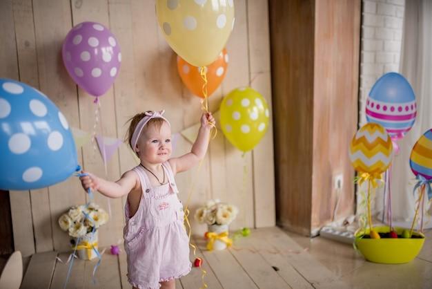 Menina encantadora parece feliz brincando com balões coloridos