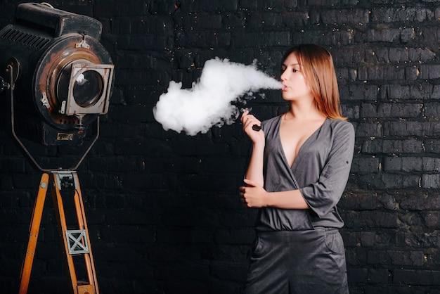 Menina encantadora pensativa, fumando um cigarro eletrônico, uma nuvem de fumaça, tiro de foto no estúdio com câmera velha e parede de tijolos. mulher vestida de terno elegante