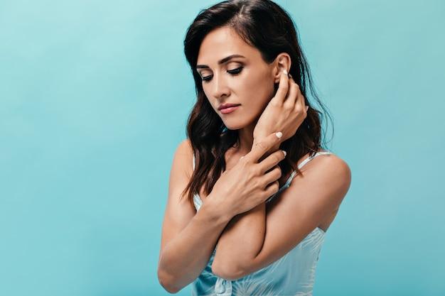 Menina encantadora posando timidamente na parede azul